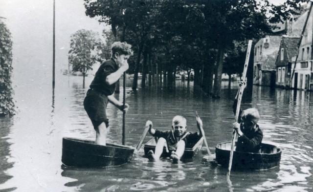 Jak widać wysoki stan Odry nie odbierał dzieciom uśmiechu. Umiejętnie wykorzystywali powódź do różnego typu zabaw, tutaj widać łodzie zrobione m.in. z bali. Zdjęcie zostało wykonane mniej więcej z okolic schodków prowadzących w stronę obecnego bulwaru Jana Pawła II. Alejka drzew widoczna na zdjęciu rośnie po dziś dzień. Z lewej strony znajduję się port rzeczny, natomiast po prawej stronie widać fragment nieistniejącego już kościółka katolickiego. Przed wojną część miasta, w miejscu której znajduje się obecny bulwar Jana Pawła II nazywano Flügel (skrzydło). Często można było tam spotkać rozstawiony cyrk, karuzelę czy też wesołe miasteczko.
