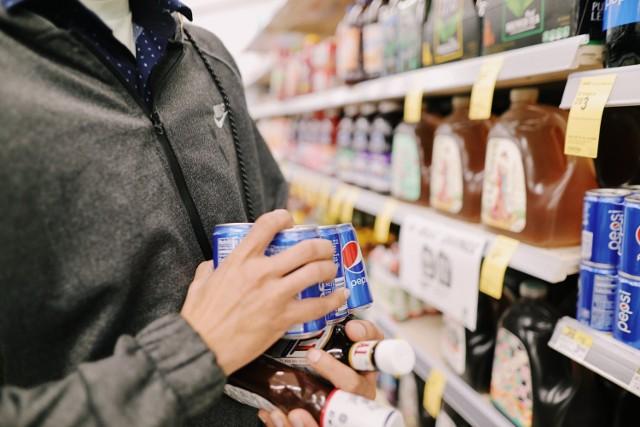 """Od początku roku w Polsce obowiązuje nowy podatek cukrowy. Podatkiem cukrowym rząd objął te napoje, które zawierają cukry i spotykaną w m.in. napojach energetycznych kofeinę i taurynę. Jeśli w słodzonym napoju jest 5 gramów cukru w 100 mililitrach, to cena litra tego napoju wzrosła o 50 groszy. Jeśli zawartość cukru w 100 ml przekracza 5 gramów, to każdy taki dodatkowy gram zwiększa podatek cukrowy od litra napoju o 5 groszy.  To nie koniec. Od początku roku obowiązuje też opłata za sprzedaż na wynos napojów alkoholowych, których pojemność nie przekracza 300 ml. Naliczana jest wg ilości 100 procentowego alkoholu w butelce o pojemności do 300 ml. Stawka bazowa to 25 zł od litra czystego alkoholu. Zatem np. jeśli w """"małpce"""" o pojemności 100 ml jest 40 procentowa wódka, to kupując taką butelkę trzeba zapłacić od nowego roku o 1 zł więcej.   W założeniu nowe podatki i wzrost cen mają promować zdrowszy sposób odżywiania.  Jak zmieniły się ceny? Te sklepy, które mogły sobie na to pozwolić, zrobiły duże zakupy jeszcze w ubiegłym roku, aby stopniowo i rozkładając w czasie zwiększać ceny. Inne z każdą nową dostawą produktów objętych nowymi podatkami zmieniają etykiety z cenami.   Sprawdziliśmy w kilku osiedlowych sklepach we Wrocławiu, jak wzrosły ceny popularnych napojów w pierwszych dniach nowego roku.   Zobacz na kolejnych slajdach - posługuj się myszką, klawiszami strzałek na klawiaturze lub gestami"""