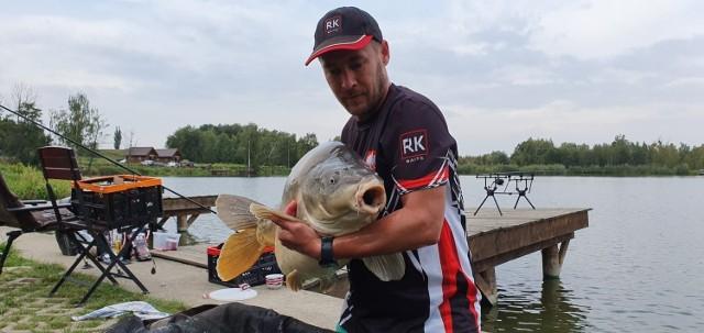 Jakub Pławny z największym karpiem, jaki do tej pory złowił. Ryba ważyła blisko 25 kilogramow.