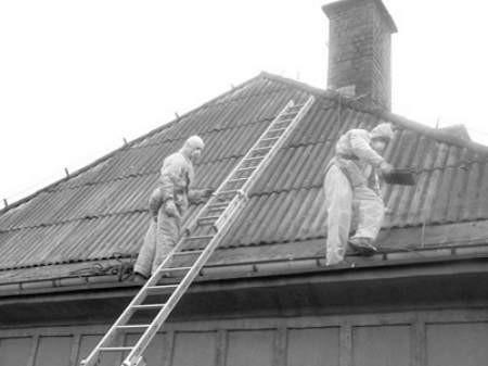 Aleksander Sosnowski i Grzegorz Biernacki ściągają z dachu azbestowe płytki.