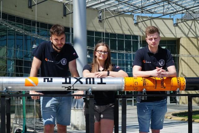 Ponad 4-metrową rakietę skonstruowali poznańscy studenci Politechniki. Ich zespół badawczy PUT Rocketlab, weźmie udział w prestiżowych zawodach międzynarodowych - IREC Spaceport America Cup 2021 - w których powalczy z takimi uczelniami jak Stanford czy Waszyngton. Jako jedyna drużyna z Polski, team będzie startować w najbardziej zaawansowanej kategorii.   Na zdjęciach widać od lewej Pawła Janusiaka, przewodniczącego PUT Rocketlab, Luizę Rybarczyk, członkinię zespołu oraz Krystiana Kutnika, wiceprzewodniczącego