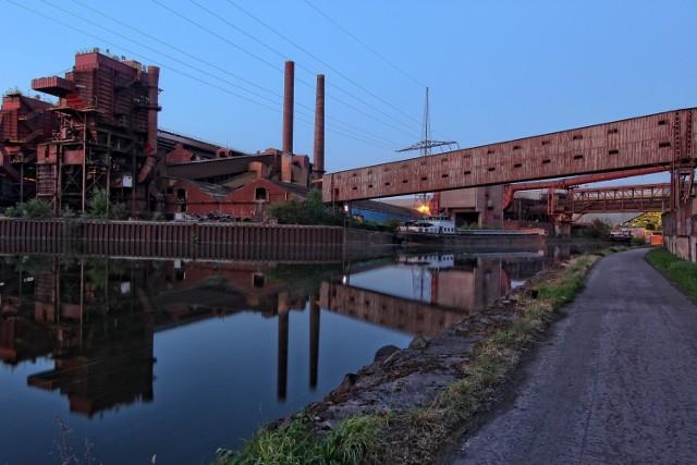 """1. Charleroi w Belgii.   Kilka lat temu miasto Charleroi zostało nazwane przez stację BBC najbrzydszym miastem na świecie. Jest ono położone w południowej, francuskojęzycznej części Belgii w regionie Walonii. Dawniej było ośrodkiem przemysłowym pełnym kopalń węgla kamiennego i zakładów przemysłu ciężkiego. Kryzysu ekonomiczny sprawił, że wiele z nich upadło. Ponurą sławę przyniósł miastu także dom seryjnego mordercy Marca Dutrouxa, w którym torturował swoje ofiary.  Obecnie Charleroi świetnie kojarzą turyści korzystający z tanich linii lotniczych, ponieważ pełni funkcję portu obsługującego Brukselę oraz dogodnego punktu przesiadkowego. W przerwie pomiędzy lotami można np. skorzystać z usług największego w Europie tunelu aerodynamicznego przeznaczonego do skoków spadochronowych. Ceny biletów zaczynają się od 59 euro. Miłośnicy zwiedzania mogą natomiast wybrać się do jednego z czterech muzeów. Ciekawą atrakcją jest także miejski ratusz, posiadający aż 47 dzwonów. Co godzinę odgrywają one melodię piosenki """"Land of Charleroi – to ciebie kocham najbardziej"""""""