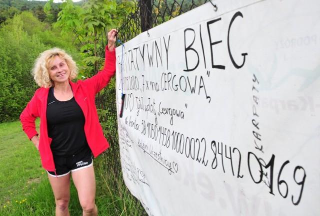 Izabela Zatorska-Pleskacz przy białej płachcie, na której składają swoje podpisy wszyscy biegacze startujący w akcji charytatywnej