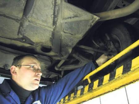 Tomasz Cwajna naprawia zawieszenie zniszczone na dziurawej drodze.