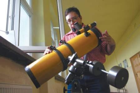 Mariusz Chirowski przygotowuje teleskop do obserwacji nieba.