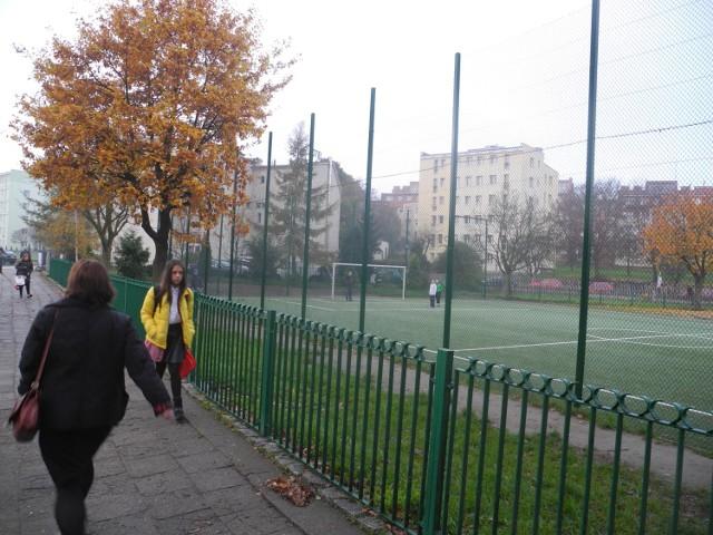 Uczniowie grają w piłkę bez siatek na bramkach. Ale piłka nie wylatuje na drogę, bo boisko jest ogrodzone.