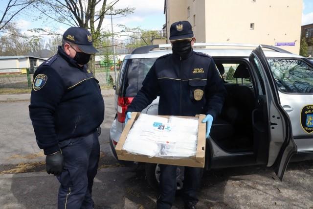 Strażnicy miejscy rozdają maseczki ochronne w Legnicy.