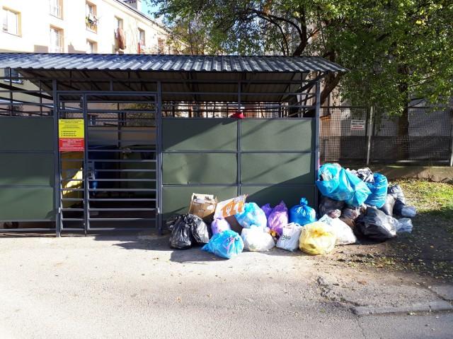 Wiata śmietnikowa zamknięta, a worki ze śmieciami piętrzą się obok.