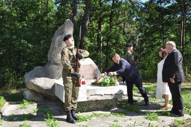 Przed obeliskiem na Czerwonym Krzyżu w lesie przy drodze Staszów Osiek kwiaty składają: starosta staszowski Michał Skotnicki, członek Zarządu Powiatu w Staszowie Jerzy Chudy i dyrektor staszowskiego liceum Anna Karasińska.