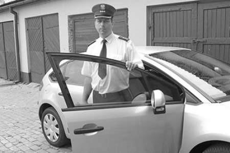 Komisarz Grzegorz Olejniczak przy nieoznakowanym radiowozie. Olgierd Górny
