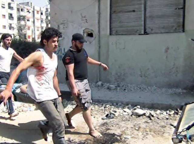 """Film walczy o nagrodę główną festiwalu.   Nagradzany na całym świecie – od Sundance po Kraków – dokument Talala Derkiego ukazuje syryjski konflikt w takim zbliżeniu, że widzowie czują się jak na pierwszej linii frontu.   Twórcy filmu niejednokrotnie ryzykowali życiem, rejestrując walki w oblężonym mieście. Ale o niezwykłej mocy Powrotu do Homs decyduje jego główny bohater: Abdul Basit Saroot – znany i lubiany w rodzinnym Homs piłkarz młodzieżowej reprezentacji Syrii, dziewiętnastolatek o niespożytej energii i zadziwiającej charyzmie.   Kiedy zaczyna się syryjska rewolucja, wymyślane przez niego na poczekaniu slogany w mgnieniu oka podchwytują demonstrujące przeciw reżimowi Assada tłumy.   Kiedy zaś syryjski konflikt wkracza w kolejną fazę i na ulice wyjeżdżają czołgi, """"śpiewający bramkarz"""" – podobnie jak wielu innych – chwyta za broń.  Nieustannie igra ze śmiercią w mieście, które coraz bardziej przypomina warszawskie morze ruin z jesieni 1944 roku.   Jego wyczyny przechodzą do legendy: wielokrotnie ranny cudem wymyka się z kolejnych okrążeń, ale wciąż powraca do walki – i miasta, które wbrew wszystkiemu stawia opór wojskom reżimu.   Bez wątpienia """"Powrót do Homs"""" pozostanie jednym z najwybitniejszych filmowych świadectw walki Syryjczyków o wolność."""