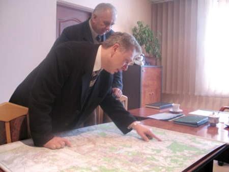 Dariusz Zawadzki, komendant powiatowy PSP i Bogdan Ociepka, pracownik Starostwa Powiatowego wspólnie zaznaczaja na mapie najbardziej zagrożone powodzią miejsca.