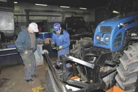 Krzysztof Iwański i Stefan Piasecki w bazie Alby MPGK przygotowują do wyjazdu w teren ciągnik, wyposażony w pług.