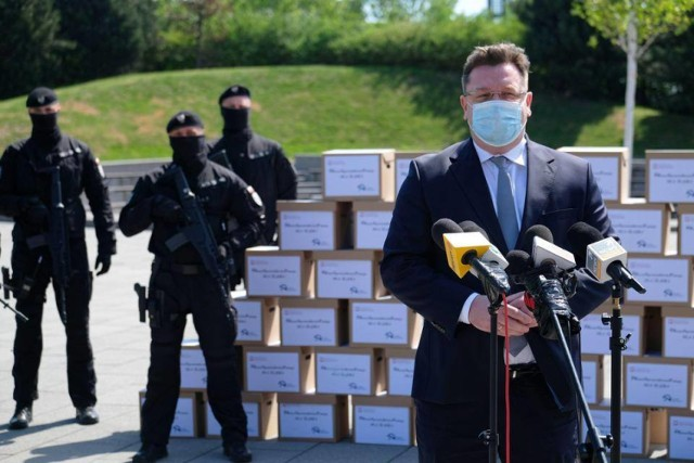 Na zdjęciu widać funkcjonariuszy Służby Więziennej przy kartonach, w których miały znajdować się maseczki ochronne