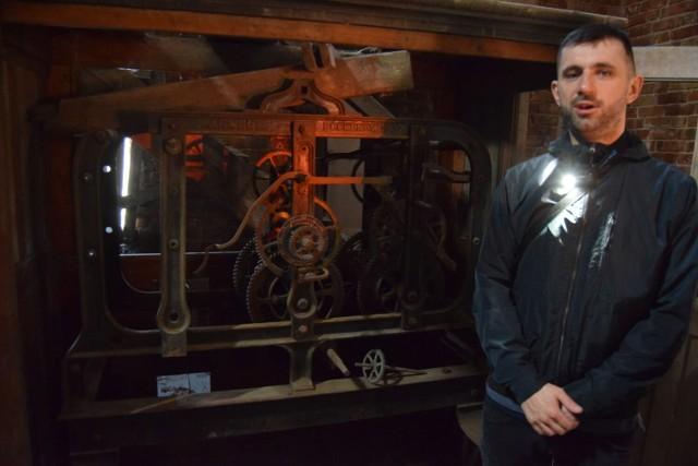 Mateusz Zacharewicz na tle uszkodzonego mechanizmu zegara w kościele Mariackim