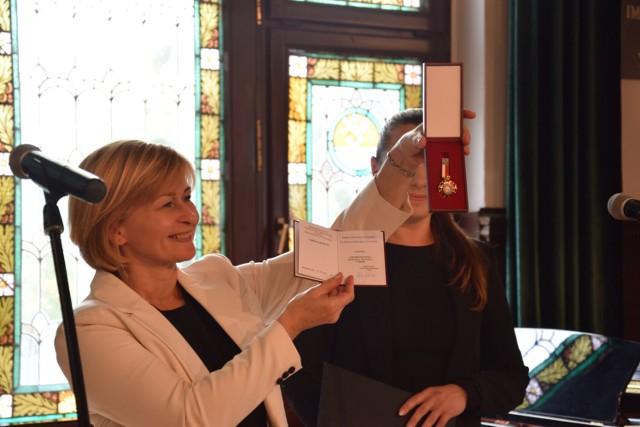 Dyrektor PSM Agnieszka Orłowska prezentuje honorową odznakę Zasłużony dla kultury polskiej przyznanej szkole przez ministra kultury