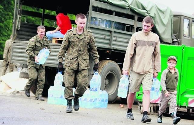 Żołnierze rozpakowują dary i dostarczają je ludziom