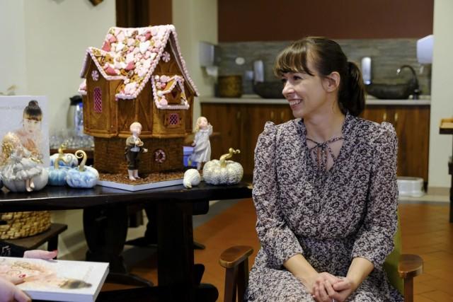 """Dziś (13.08.) w Muzeum Toruńskiego Piernika odbyło się spotkanie z Jowita Woszczyńską - mistrzynią świata w dekorowaniu tortów 2019. Podczas spotkania wirtuozka cukiernictwa opowiadała o swojej pracy, a także o swojej książce """"Sugar Fairy Tales"""". Znajdziemy w niej mnóstwo wskazówek, praktycznych przykładów technik i ciekawostek z zakresu sugarcraftingu.  Książka przenosi nas w magiczny, baśniowy świat, w którym poznajemy historię powstawania niesamowitych cukierniczych dzieł sztuki.  Jowita Woszczyńska poprowadziła także krótki pokaz dekorowania.  Zobacz też:  Jak spędzić weekend w Toruniu. Możliwości jest wiele"""