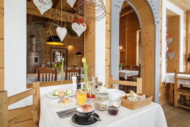 Restauracja Zakopiańska  Ul. Jagiellońska 18, Zakopane   Restauracja Zakopiańska to znakomita kuchnia i przytulne wnętrza w starym góralskim domu wybudowany w stylu zakopiańskim. Jak mówi właściciel restauracji Tomasz Gut, to pierwsze na Podhalu miejsce, które nie podlega prostemu szufladkowaniu – Zakopiańska to elegancka restauracja, która nie onieśmiela cenami ani wystrojem; winiarnia, w której nie trzeba być sommelierem by skosztować wybornego trunku; bistro, do którego na lunch zaglądają lokalni biznesmeni i goście wypoczywający pod Tatrami. Specjalnością kuchni jest gęsina, jagnięcina, kaczka, ale także górski pstrąg. I cała paleta tradycyjnych góralskich produktów.