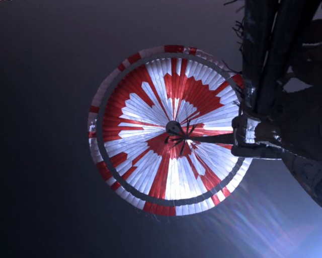 Moment opuszczania statku z łazikiem na powierzchnię Marsa. Kamera jest zamontowana na tylnej części statku kosmicznego i pokazuje czaszę spadochronu użytego do amortyzacji lądowania.