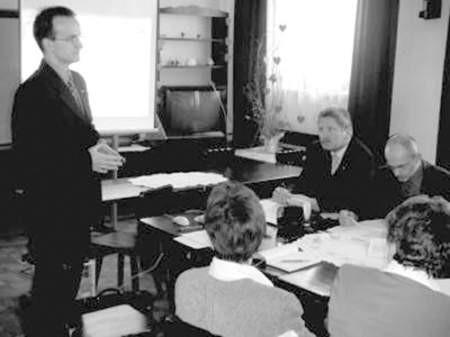 Rafał Adamczyk przedstawia strategiczne cele sławkowskiego samorządu. Za stołem siedzą burmistrz Bronisław Goraj i jego zastępca Zbigniew Tarmas. Tyłem pracownice magistratu: Helena Spodymek i Alicja Lipska.
